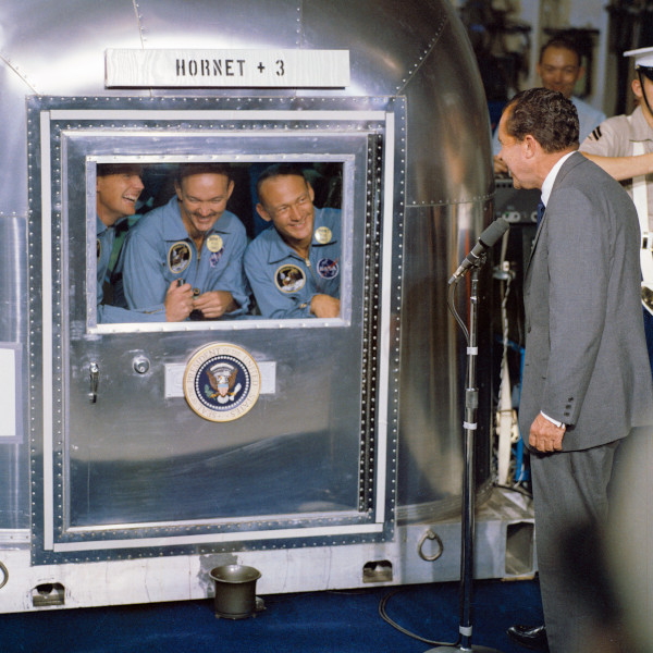 image President Nixon addresses the Apollo 11 crew in the Mobile Quarantine Facility. The mission patches that can be seen are of the same design as the one in the National Space Centre's collection - Credit: NASA