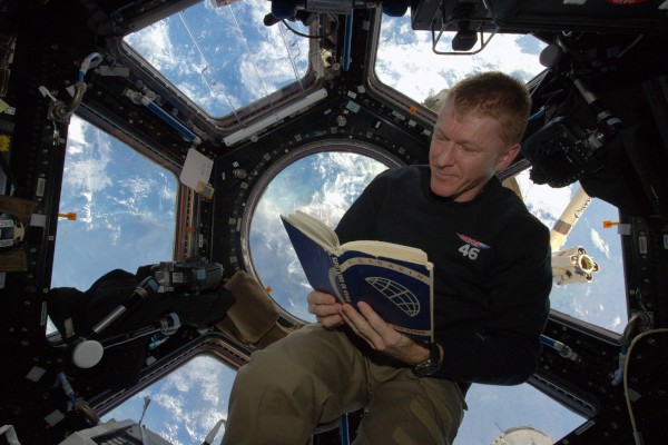 image Tim Peake with the book in the Cupola of the International Space Centre - Credit: ESA