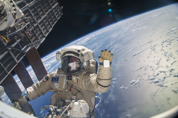 image Sergey Ryanzanskiy waves in his Orlan MK Spacesuit. Note the mirror on his left sleeve, used to help read the controls on the chest of his suit, which are written in reverse - Credit: NASA